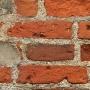 """Widoczne w cegłach małe otwory to ślady po stosowanej w średniowieczu pokucie, polegającej na wierceniu godzinami palcem w cegle. Mocna ceramiczna cegła nie poddawała się łatwo tej morderczej """"obróbce"""". Była to surowa lekcja pokory widziana przez innych parafian."""