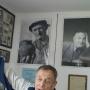 Pan Wiktor Litwińczuk na tle fotografii swojego ojca, założyciela zbiorów.