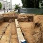 Widoczny ułożony stos kamieni to fundamenty na których stał niegdyś budynek kostnicy. Z lewej strony fragmenty muru cmentarza.