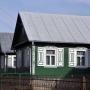 Drewniana zabudowa. Rząd ustrojonych bogatymi zdobieniami domów rozpoczyna się na posesji nr 12.