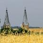 Idąc od południa zza łanów zbóż wyłaniają się wieże kościoła św. Anny.