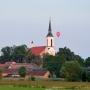Wiejskie chaty wśród soczystej, wiosennej zieleni, kościół w ostatnich promieniach słońca i....balon?