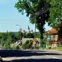 Supraski Monaster od strony ul. Piłsudskiego wydaje się unosić nad zielenią drzew.