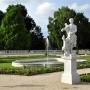 Rzeźba ogrodowa i fontanna w tle.
