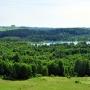 Centralna część widoku odkrywa przed nami niewielkie jezioro Purwin (ukryte w lesie), za nim po prawej jez. Kolie i obok Perty za nimi pasmo niewielkich wzgórz. W oddali za nimi widać samotnie stojącą, najwyższą w tej okolicy Górę Cisową (256,4m).