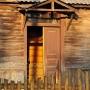 Skromne wejście domu przy ul. Skorupskiej 46 oświetlone zachodzącym słońcem.